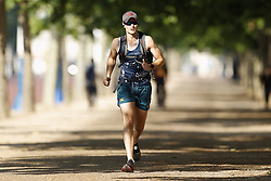 © Licensed to London News Pictures. 24/06/2020. London, UK. Joggers make the most of early morning sunshine on The Mall in central London. High temperatures and sunshine are expected in most of the UK over the next few days. Photo credit: Peter Macdiarmid/LNP