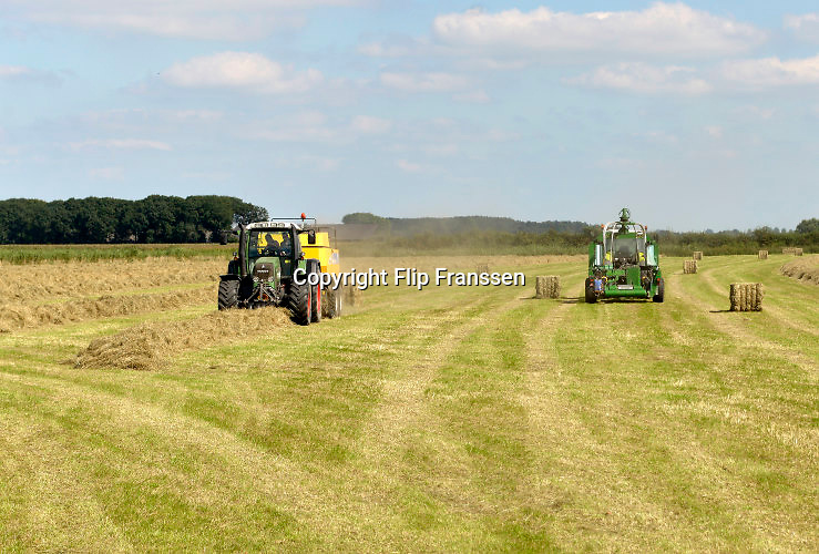 Nederland, Ubbergen, 1608-2016In de Ooijpolder maakt een boer gebruik van het mooie weer om gras te maaien. Daarna wordt het tot balen gepakt en later als wintervoer aan het vee, de koeien, gevoerd. Foto: Flip Franssen