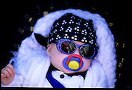 Baby in sunglasses wears blue scarf and sash as a fan of one of Padstow's two May Day hobby horses; Cornwall, England.