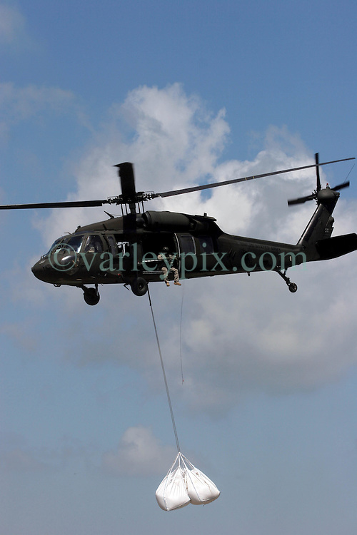 12 june 2010. Wetlands of Plaquemines Parish, South Louisiana. <br /> An army blackhawk on a sandbagging mission. Sand bags attempt to join the dots and connect what little remains of fragile barrier islands. It is unlikely the bags will survive a hurricane. Where once there was land, there is only the mere outline of old canals and channels, many dug by oil companies to pump their product ashore with little regard to the effects the chopping up of the wetlands would have. Chronic erosion of the land, a football pitch every 50 minutes, greatly reduced protection from hurricanes and impending BP oil slicks is the direct result of mismanagement and utter disregard for the environment. The army corps of engineers and the oil companies, together with inept government have a great deal to answer for. <br /> View from a blackhawk helicopter flown by airmen of the Nebraska Air National Guard over southern Louisiana as they assist in the dumping of sand bags onto barrier islands in a vain attempt to prevent BP oil from getting into the inner  wetlands. As valiant as their efforts are, the dumping of sand bags may well prove to be a complete waste of manpower, resources and money. A hurricane will likely roll over and blast through any sandbag 'barrier island,' blowing thousands of large white plastic bags far and wide across the landscape. That will really help the environment! <br /> Meanwhile, the mighty Mississippi river runs straight out to sea nearby, her valuable land building sediment carried far out into deep ocean as the region struggles to find a way to reverse the disastrous effects of man's interference with her flow. <br /> Photo credit; Charlie Varley/varleypix.com