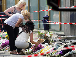 © Licensed to London News Pictures . FILE PICTURE DATED 15/07/2013 . Oldham Street , Manchester , UK . Stephen Hunt's family look at flowers and tributes at the scene . Daughter Charlotte (black and white sleeveless top, black pants, 18), sister Sarah (cream sleeveless top, blue jeans, dark hair, sunglasses) and ex-wife Zoe (white top, black pants, sunglasses) . The scene on Oldham Street following a fire at Paul 's Hair World on 13th July which claimed the life of fireman Stephen Hunt . Photo credit : Joel Goodman/LNP