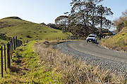 Pickup driving around bend on unsealed road New Zealand