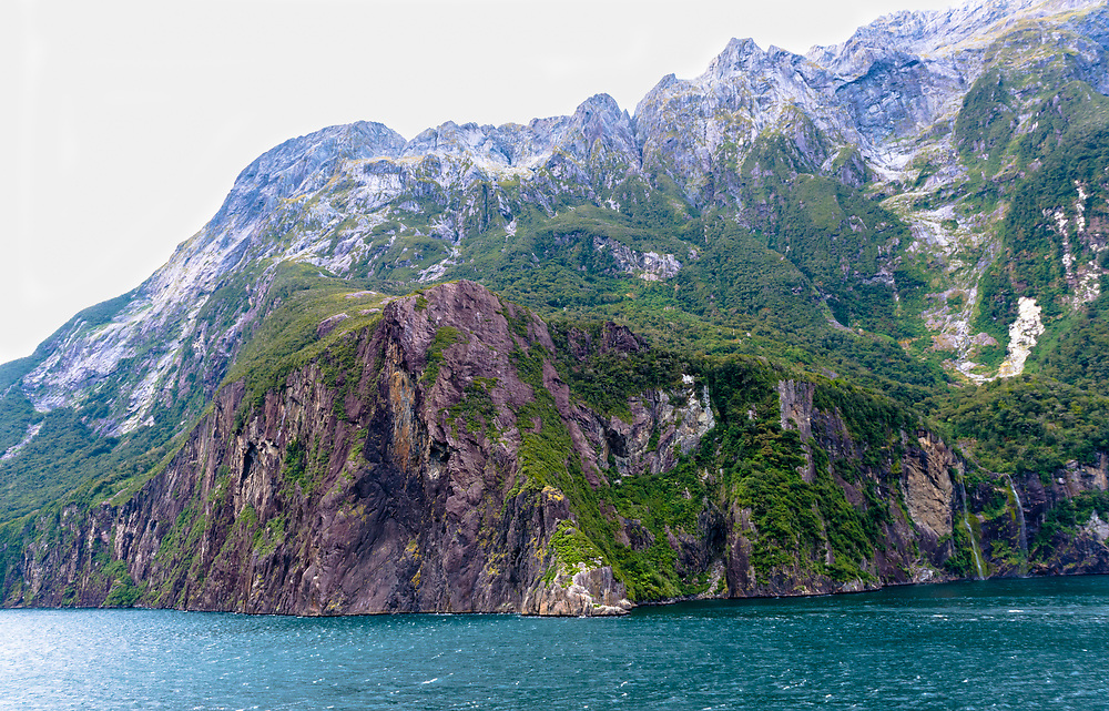 Water from the Fiord laps up against the baseline of a mountain.