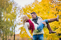 Portrait of handsome mature man carrying his wife while walking in park