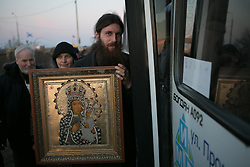 A Christians orthodox holds a religious canvas after doing a prayer and blessing a checkpoint in front of a military base controlled by armed men believed to be Russian and Crimean pro-Russian volunteers. Ukraine , Thursday, 13th March 2014. Picture by Daniel Leal-Olivas / i-Images