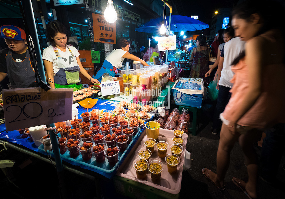 A food stall selling grilled meats, fish and fresh juices at the calm and atmospheric walking night market along Wualai Road in Chiang Mai, Thailand.