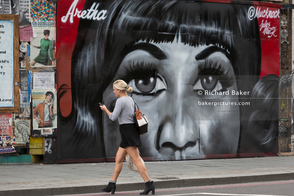A Londoner crosses the road past a recent mural in Shoreditch (by artist Jules Muck) of Soul Queen Aretha Franklin who died a few days earlier, on 20th August 2018, in London, England.