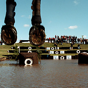 A gallery of spectators surround the water jump as a horses hooves appear over the jump at Lochinvar during an equestrian three day event.