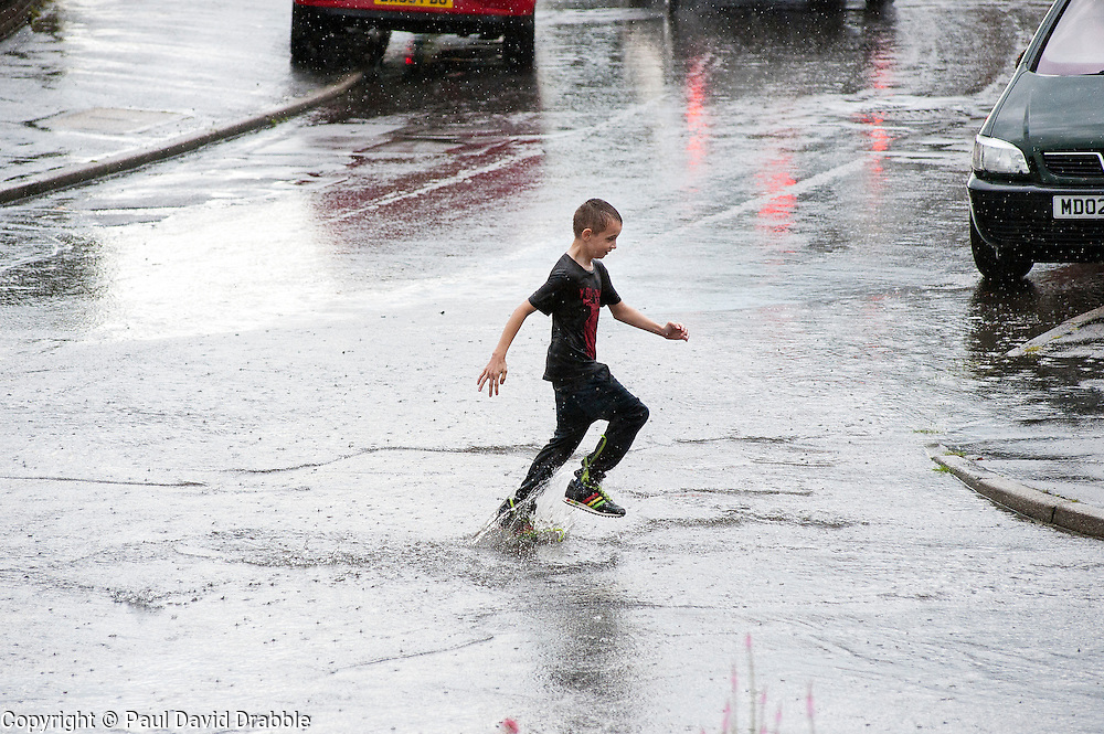 16:43 Ecclesfield Sheffield UK.A saturated young boy crosses Minster road..5 July 2012.Image © Paul David Drabble