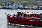 An old Chicago Fire Department boat currently used as an excursion boat passes a docked Coast Guard boat in Sturgeon Bay in Door County, Wisconsin.