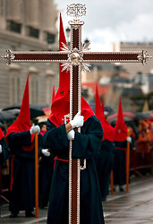 A participant wearing a traditional nazareno or penitential robe marches in procession during Holy Week in Madrid, Spain.