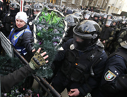 March 23, 2019 - Kiev, Ukraine - Supporters of the Ukrainian far-right party National Corps throw wreaths to riot police officers who secure the Ukrainian President's office, during an anti-corruption rally in Kiev, Ukraine, 23 March, 2019. The protesters are demanding strict punishment for Ukrainian President Petro Poroshenko's allies, who they accuse of profiting from the sale of smuggled Russian military parts to state defence companies at inflated prices. (Credit Image: © Str/NurPhoto via ZUMA Press)
