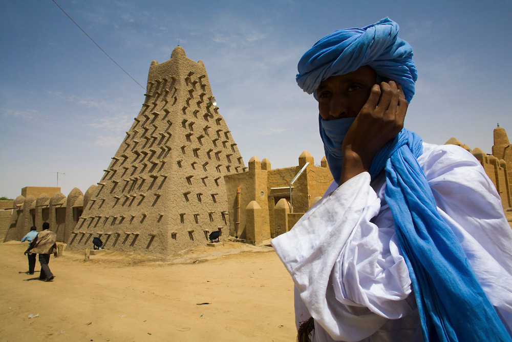 A man wearing tuareg clothing talks on the phone in front of Sankor�osque, in Timbuktu, Mali.
