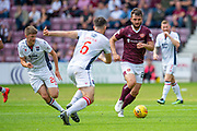 Craig Halkett (#26) of Heart of Midlothian FC runs forward as Ross Draper (#6) and Blair Spittal (#20) of Ross County FC watch on during the Ladbrokes Scottish Premiership match between Heart of Midlothian and Ross County at Tynecastle Stadium, Edinburgh, Scotland on 10 August 2019.