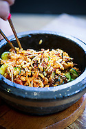 Bibimbap is a popular Korean dish that is served with warm rice mixed with a wide variety of ingredients, usually beef and vegetables. Seoul, South Korea