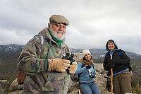 Senior man holding binoculars in mountains