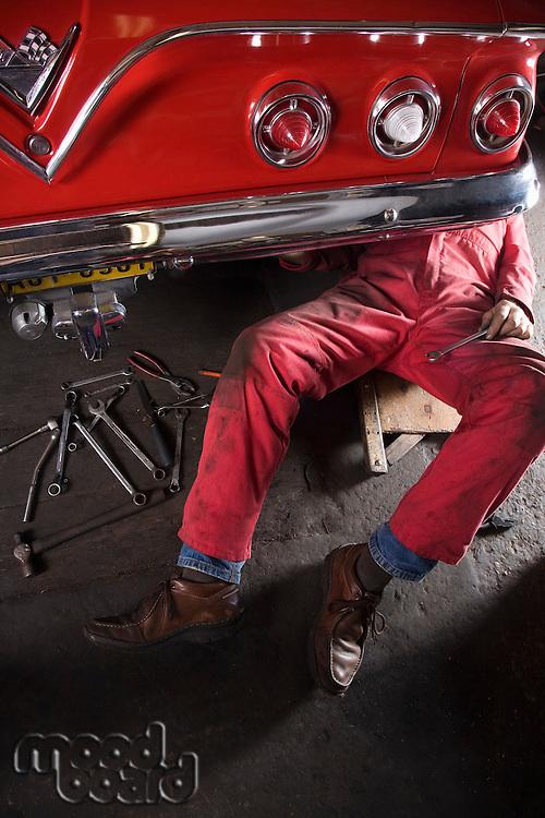 Mechanic working Under Back of Vintage Car