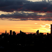The sun sets behind the Manhattan skyline in New York City viewed from Flushing, Queens, New York. USA. Photo Tim Clayton