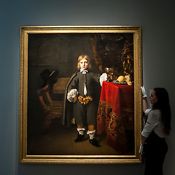 "© Licensed to London News Pictures. 06/07/2015. London, UK.  A Sotheby's technician shows Fernando Bol's ""Portrait of a boy, said to be the artist's son aged 8"" (est. £2m to £3m) at the preview of Old Masters, British Paintings and Masterworks from the collection of Castle Howard at Sotheby's ahead of the auction on July 8. Photo credit : Stephen Chung/LNP"