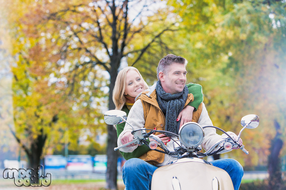 Portrait of mature man driving motorbike with his wife in park