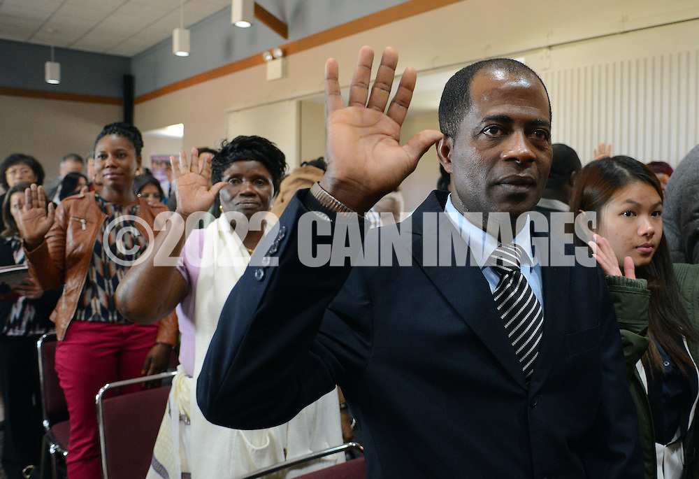 DUBLIN, PA - OCTOBER 24: Pedro Cano (C) of the Dominican Republic takes the Oath of Citizenship along with fellow applicants during a Naturalization ceremony October 24, 2014 at the Pearl S. Bucks House in Dublin, Pennsylvania. 48 applicants from 28 countries were naturalized during the ceremony, and became U.S. citizens. (Photo by William Thomas Cain/Cain Images)
