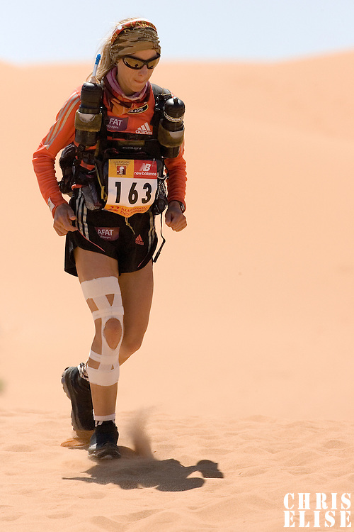 30 March 2007: 2006 winner of the women race #163 Geraldine Courdesses of France runs over a dune in erg Znaigui en route to check point 3 during fifth stage of the 22nd Marathon des Sables between west of Kfiroun and erg Chebbi (26.22 miles). The Marathon des Sables is a 6 days and 151 miles endurance race with food self sufficiency across the Sahara Desert in Morocco. Each participant must carry his, or her, own backpack containing food, sleeping gear and other material.