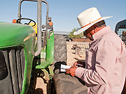 31 JULY 2009 --  BUCKEYE, AZ: Alex Flores, (CQ) from Laredo, TX, looks at equipment before bidding at the auction on the former Pylman Dairy Farm in Buckeye. The auction was handled by Overland Stockyards from Hanford, CA. The Arizona dairy industry is struggling to survive the worst milk economy some have ever seen. Due to the global recession, overseas demand for Arizona dairy products has plummeted, forcing prices down while production costs have stayed stable or gone up. For every $1 dairymen earn from milk sales, it cost them $1.50 to produce the milk. Photo by Jack Kurtz