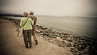 An elderly couple walk down a path near Crissy Field, San Francisco, California, USA.