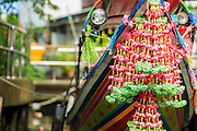 "17 NOVEMBER 2012 - BANGKOK, THAILAND:  Flowers on the prow of a ""long tailed"" boat in Bangkok. Long tailed boats use big V8 car engines and have 30-40 foot long propeller shafts that extend past the back of the boat. Bangkok used to be known as the ""Venice of the East"" because of the number of waterways the criss crossed the city. Now most of the waterways have been filled in but boats and ships still play an important role in daily life in Bangkok. Thousands of people commute to work daily on the Chao Phraya Express Boats and fast boats that ply Khlong Saen Saeb or use boats to get around on the canals on the Thonburi side of the river. Boats are used to haul commodities through the city to deep water ports for export.    PHOTO BY JACK KURTZ"
