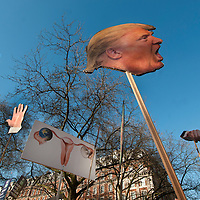 London UK. January 21st 2017.An estimated 100,000 protesters took part in a Women's March from the US Embassy in Grosvenor Square to Trafalgar Square as part of an international campaign on the first full day of Donald Trump's Presidency of the United States.  A group hold Trump's head on a stick, his hands and a placard showing a woman's reproductive organs, referencing  fears that Trump will overturn the Affordable Care Act and thus threaten reproductive health care.