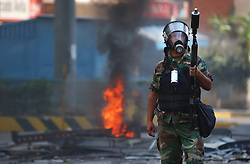 A member of the National Guard waits to fire tear gas at  anti-government protestors  as riots continued in Caracas between the two groups. The country is awaiting a preliminary decision on the validity of signatures seeking a recall referendum.  It is expected that hundreds of thousands of signatures will have to go to a review process that the opposition will refuse to submit to.