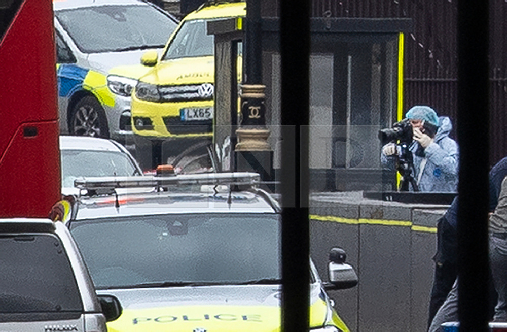 © Licensed to London News Pictures. 14/08/2018. London, UK. A police forensics officer is seen near the silver car (L-next to red London bus) that crashed into barriers outside Parliament. A number of pedestrians are injured. The driver was arrested.  Photo credit: Peter Macdiarmid/LNP
