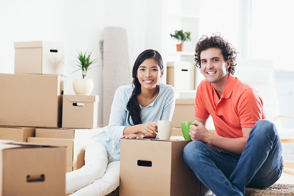 Young multi-ethnic couple having a break while moving into their new home.