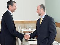 Businessmen shaking hands in restaurant