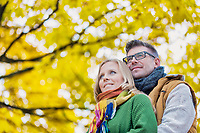Portrait of handsome man embracing his wife from the back in park
