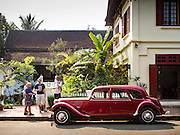 "13 MARCH 2016 - LUANG PRABANG, LAOS:  Tourists look at a 1952 Citroen Model 11, one of only two of that model in Laos, at 3 Nagas, one of the most upscale hotels in Luang Prabang. Luang Prabang was named a UNESCO World Heritage Site in 1995. The move saved the city's colonial architecture but the explosion of mass tourism has taken a toll on the city's soul. According to one recent study, a small plot of land that sold for $8,000 three years ago now goes for $120,000. Many longtime residents are selling their homes and moving to small developments around the city. The old homes are then converted to guesthouses, restaurants and spas. The city is famous for the morning ""tak bat,"" or monks' morning alms rounds. Every morning hundreds of Buddhist monks come out before dawn and walk in a silent procession through the city accepting alms from residents. Now, most of the people presenting alms to the monks are tourists, since so many Lao people have moved outside of the city center. About 50,000 people are thought to live in the Luang Prabang area, the city received more than 530,000 tourists in 2014.   PHOTO BY JACK KURTZ"