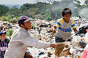 09 NOVEMBER 2004 - TAPACHULA, CHIAPAS, MEXICO: Carlos Lopez Perez, 12, right, and an adult pick through the garbage in the municipal garbage dump in Tapachula, Chiapas, Mexico. About 130 people, the poorest of the poor in Tapachula, work in the dump picking through the garbage hoping to find tidbits they can use or sell to brokers who sit on the edge of the dump and resell the garbage. Most of the dump workers are Guatemalan migrants who crossed the border hoping, at one time, to get to the United States. Now they have settled for an existence on the very edge of Mexican society. PHOTO BY JACK KURTZ
