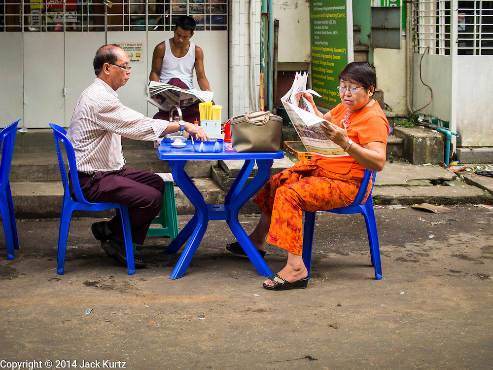 02 NOVEMBER 2014 - YANGON, MYANMAR: A couple has breakfast in a tea stand in the 38th Street morning market in downtown Yangon, Myanmar. The market is typical of morning markets in Yangon, a city coming out of more the 50 years of economic isolation. Most people still shop in markets because Yangon does not have as many grocery stores as Bangkok, Kuala Lumpur or many other large cities.     PHOTO BY JACK KURTZ