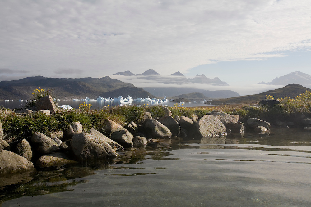 Greenland, Unartoq Island, Morning sun lights natural hot springs on summer morning