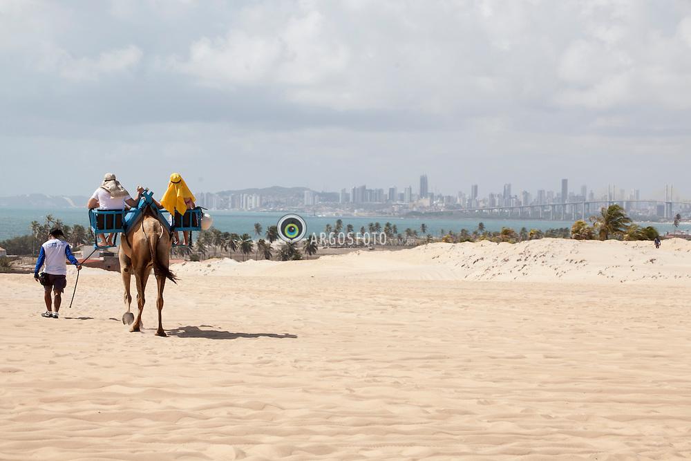 Casal passeando com dromedario no alto da Praia de Genipabu./ Couple walking in camel in Upper of Genipabu Beach. Rio Grande do Norte, Brasil - 2013.