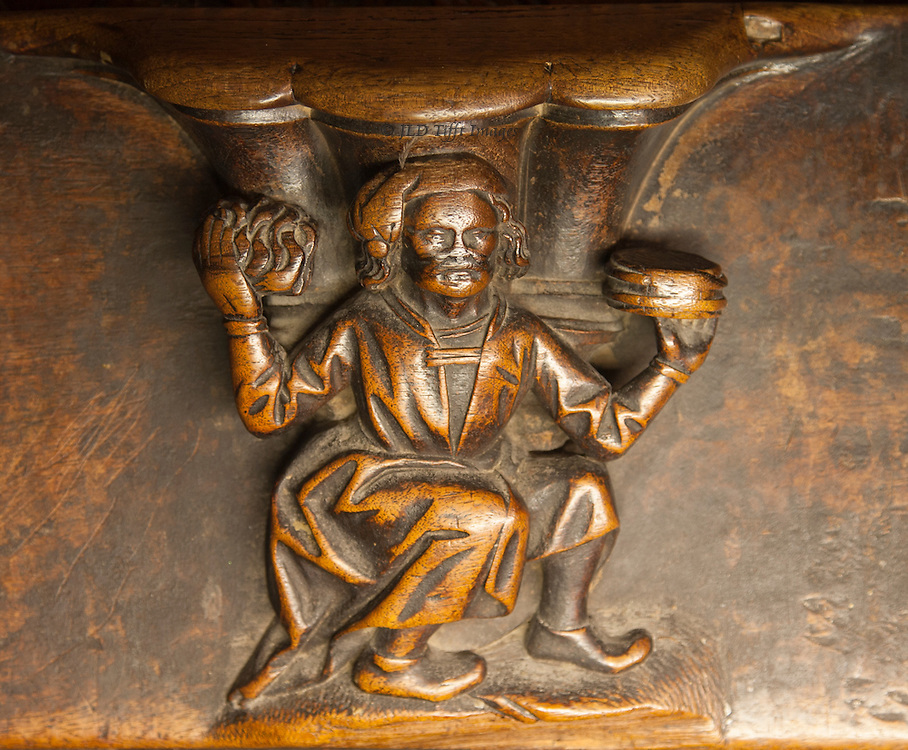 Misericord in the choir of Toledo Cathedral showing a man with a loaf of bread (?) in each hand, as though offering them for sale or delivery.