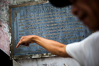 A man points to names on a mass grave site in Quang Tri province in central Vietnam.