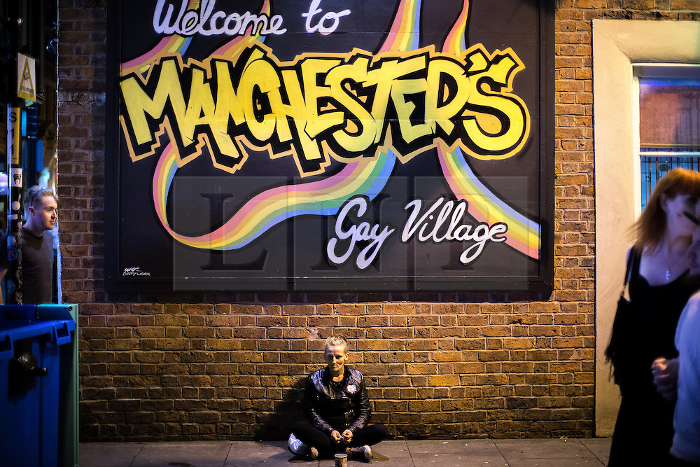 © Licensed to London News Pictures . 26/08/2016 . Manchester , UK . A woman begging for change as revellers enjoy a late night on Canal Street in Manchcester's Gay Village for 2016 Manchester Gay Pride Big Weekend . Photo credit : Joel Goodman/LNP