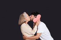 Young man kissing senior woman with red paper heart against black background