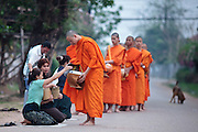 """12 MARCH 2009 -- VIENTIANE, LAOS:  Buddhist Monks in Vientiane, Laos, go about their """"Tak Bat,"""" Lao for """"monks morning rounds."""" The monks collect alms in the form of food from people who line their route. For the monks, it is the only food they get that day, for the people it's a chance to """"make merit."""" Photo By Jack Kurtz"""