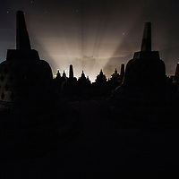 The perforated stupas of Borobudur temple are backlit from the night lights in the nearby town, Magelang, Indonesia, 2013
