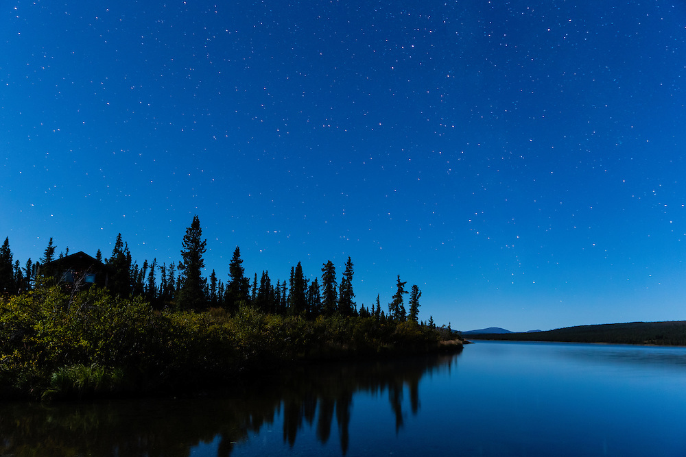 Night skies above cabin under moonlight at Paxson Lake in Southcentral Alaska. Autumn. Morning.