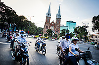 Motorbikes drive past Notre Dame Cathedral in downtown Ho Chi Minh City, Vietnam.