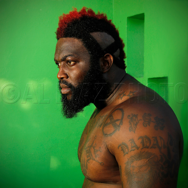 "The king of backyard brawls, mixed martial arts fighter Dhafir Harris, better known as ""DADA 5000"", captured in a state of repose adorned with tattoos, striking red hair bathed in the green cast reflected off the walls of his mothers house. <br />