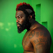 The king of backyard brawls, mixed martial arts fighter Dhafir Harris, better known as &quot;DADA 5000&quot;, captured in a state of repose adorned with tattoos, striking red hair bathed in the green cast reflected off the walls of his mothers house. <br />